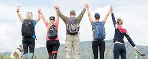 Grupo de pessoas comemorando após subir uma montanha.