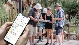 Na imagem, em primeiro plano, há um celular com horários e tela de agendamento online. Ao fundo, uma família se preparando para um passeio de ecoturismo.