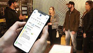 Na imagem, o foco é a tela de um celular com horários de agendamento online. Ao fundo, há uma galera jogando escape-game.