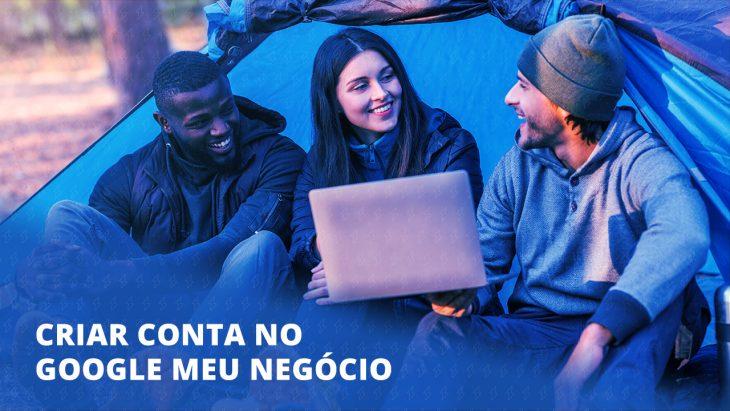 Imagem com três jovens sentados em frente a uma barraca. Um deles está com um notebook na mão e mostrando para os outros.