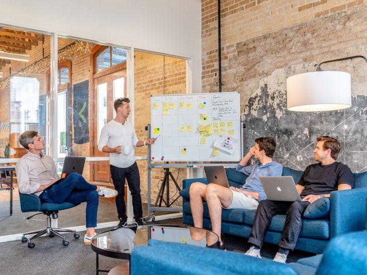 Na imagem, há 4 homens. Um deles faz um apresentação de marketing para empresas, enquanto os outros três estão sentados, assistindo.