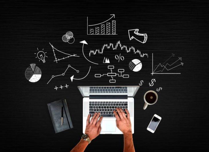 Na imagem, há um notebook fotografado de cima. Em volta do notebook, há algumas ilustrações simbolizando a atividade da tecnologia.